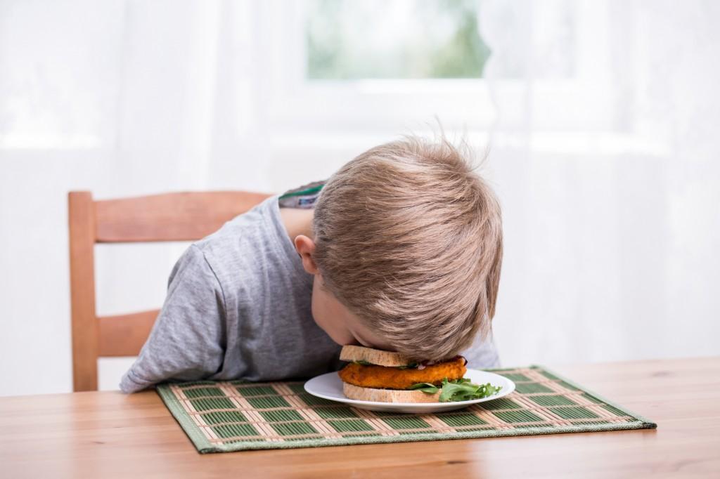 Boy landing face in food
